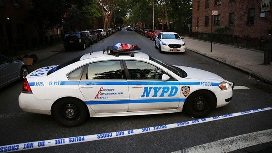 A police car is parked at a crime scene where three people were shot on June 10, 2015 in Brooklyn, N.Y.