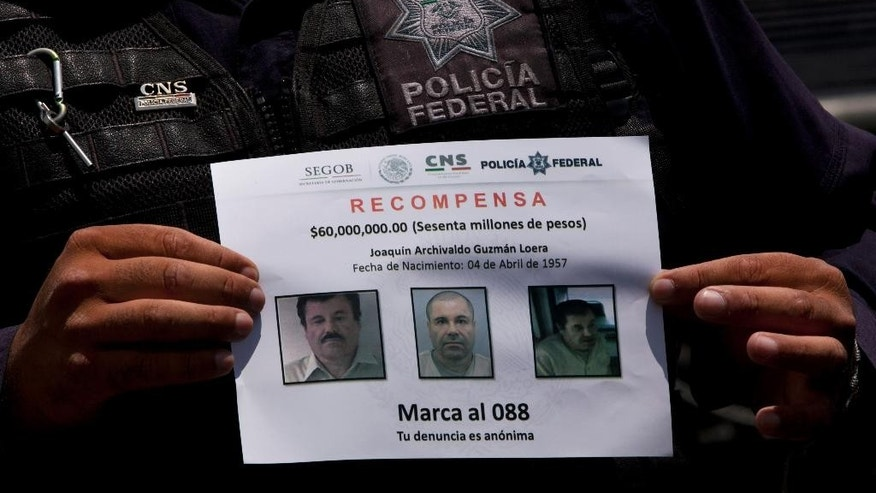 "FILE - In this July 16, 2015 file photo, a Federal Police shows a reward notice for information leading to the capture of drug lord Joaquin ""El Chapo"" Guzman, who made his escape from the Altiplano maximum security prison via an underground tunnel,  in Almoloya, west of Mexico City. (AP Photo/Marco Ugarte, File)"