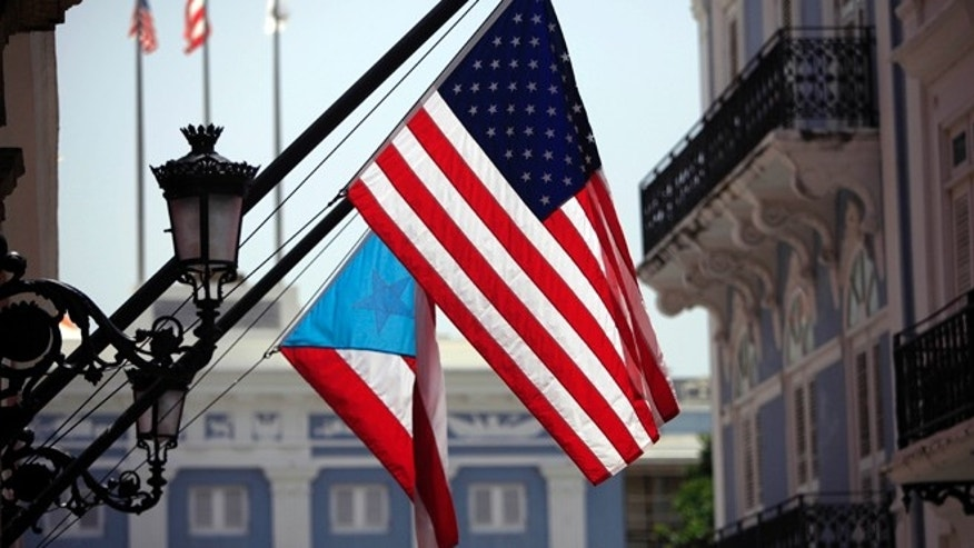 FILE - In this June 29, 2015 file photo, U.S. and Puerto Rico flags hang outside the governor's mansion in Old San Juan, Puerto Rico. Puerto Rico is entering its ninth year of recession and is struggling with billions in public debt that Gov. Alejandro Garcia Padilla has said is unpayable given the current economic conditions. (AP Photo/Ricardo Arduengo, File)