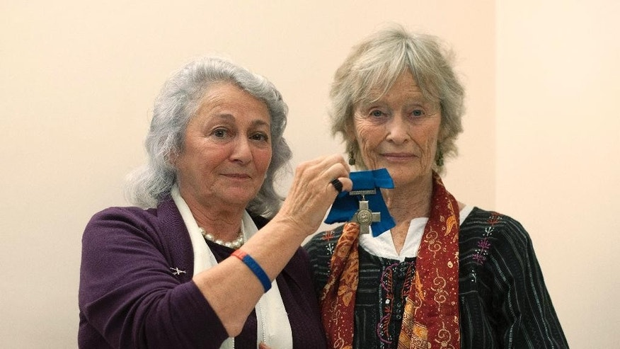 """Daughter of Violette Szabo, Tania Szabo, left, and actress Virginia McKenna who played Violette in noted 1958 movie """"Carve Her Name With Pride"""", hold the George Cross awarded to Violette, at the medal auction in London Wednesday July 22, 2015. The George Cross and four others medals awarded to the Anglo-French undercover agent, Violette Szabo, for heroism after she was captured, tortured and murdered by the Nazis in World War II, sold for 312,000 pounds (US dlrs 446,691) including commission at the auction Wednesday.  The medals are being sold by her daughter, Tania Szabo,  and will now go on display at the Imperial War Museum in London. (Lauren Hurley  / PA via AP) UNITED KINGDOM OUT - NO SALES - NO ARCHIVES"""