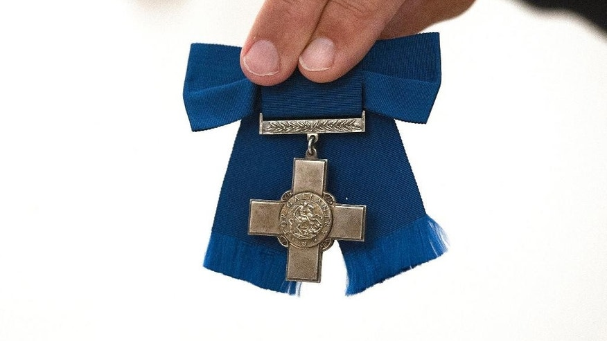 The George Cross medal awarded to Violette Szabo, is held by Dix Noonan Webb auction house employee during the auction in London Wednesday July 22, 2015. The George Cross and four others medals awarded to the Anglo-French undercover agent, Violette Szabo, for heroism after she was captured, tortured and murdered by the Nazis in World War II, sold for 312,000 pounds (US dlrs 446,691) including commission at the auction Wednesday.  The medals are being sold by her daughter, Tania Szabo,  and will now go on display at the Imperial War Museum in London. (Lauren Hurley  / PA via AP) UNITED KINGDOM OUT - NO SALES - NO ARCHIVES