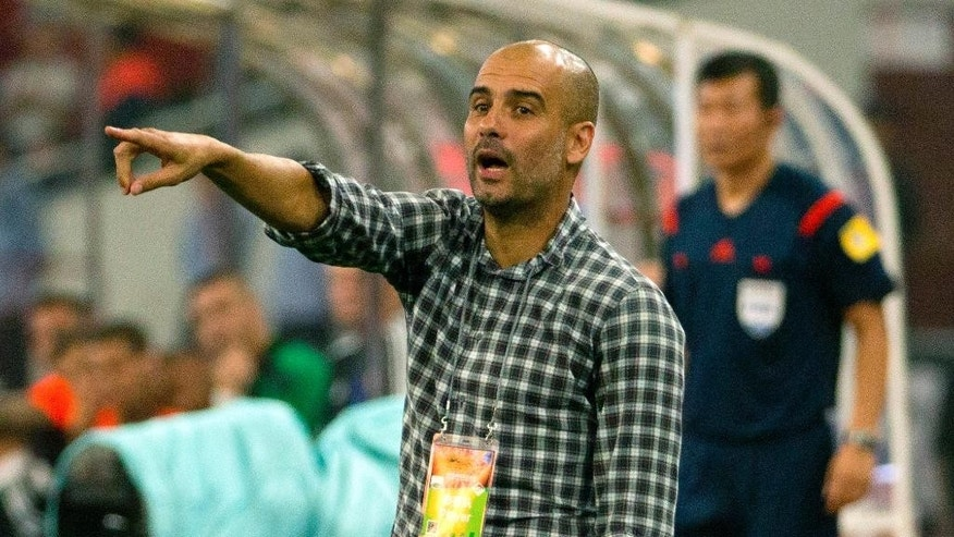 Bayern head coach Pep Guardiola gives instructions to his team during the second half of their friendly soccer match against Valencia in Beijing, Saturday, July 18, 2015. Bayern Munich beat Valencia, 4-1. (AP Photo/Mark Schiefelbein)