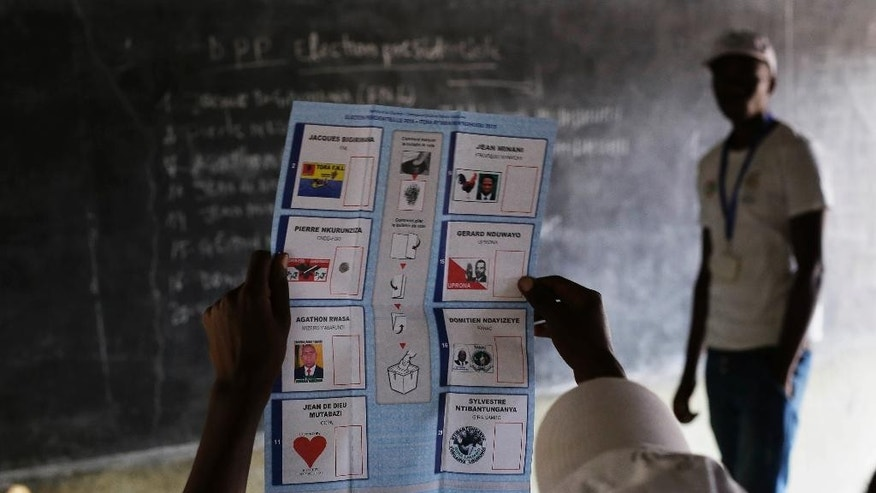 A police officer stands outside a room where tallied ballots from the Tuesday presidential elections are being stored in Bujumbura, Burundi, Wednesday July 22, 2015. The head of Burundi's electoral commission says vote counting is underway and results are expected Thursday for a controversial election in which incumbent President Pierre Nkurunziza's bid for a third term in power has sparked widespread unrest.(AP Photo/Jerome Delay)