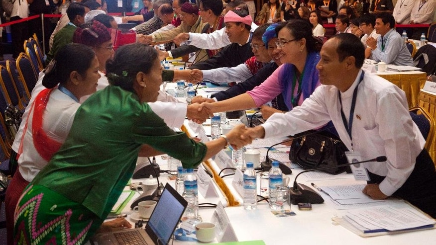 Representatives from the government's Union Peace Making Work Committee, left, and armed ethnic minority groups, right, shake hands during their meeting at Myanmar Peace Center Wednesday, July 22, 2015, in Yangon, Myanmar. They resumed critical talks on Wednesday to reach a nationwide ceasefire agreement that would end six decades of fighting before an upcoming general election that threatens to upend hard-won progress toward a deal. More than a dozen ethnic minority groups and government representatives have been in talks for more than 18 months and a key negotiator warned that failure to reach an accord could trigger a fresh round of fighting if the military takes action. The general election, which would usher in a new president, takes place in November. (AP Photo/Khin Maung Win)