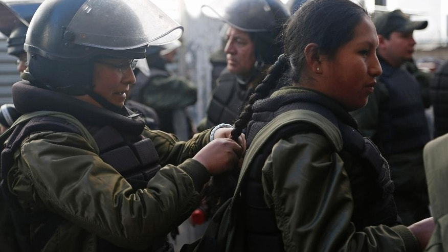 Women police in full riot gear braid each others hair before clashes with protesting miners from Bolivia's Potosi region, in La Paz, Bolivia, Wednesday, July 22, 2015. Residents in the capital city of Potosi have held a general strike for more than two weeks to pressure the national government to respond to their demands for a better hospital, an operable airport and a cement factory, among other things to revamp the economy. (AP Photo/Juan Karita)