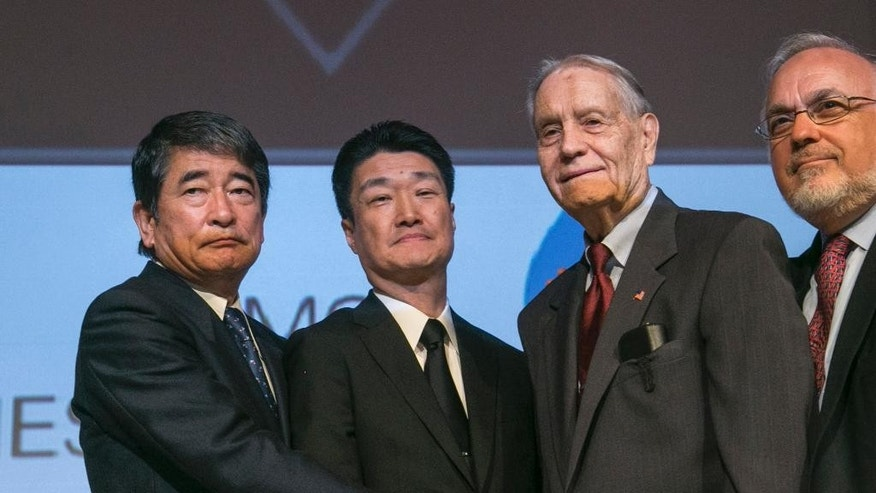 FILE - In this July 19, 2015 file photo, Yukio Okamoto, left, outside board member of Mitsubishi Materials and former special advisor to Japanese prime minister, and Hikaru Kimura, second from left, senior executive officer of Mitsubishi Materials, offer an apology as they hold hands with 94-year-old U.S. prisoner of war, James Murphy, at the Simon Wiesenthal Center in Los Angeles. Okamoto said Wednesday, July 22, 2015 in Tokyo that the company hopes to apologize to former British, Dutch and Australian World War II POWs, and also reach an amicable solution with Chinese forced laborers, following a landmark apology to American POWs earlier this week. (AP Photo/Damian Dovarganes, File)