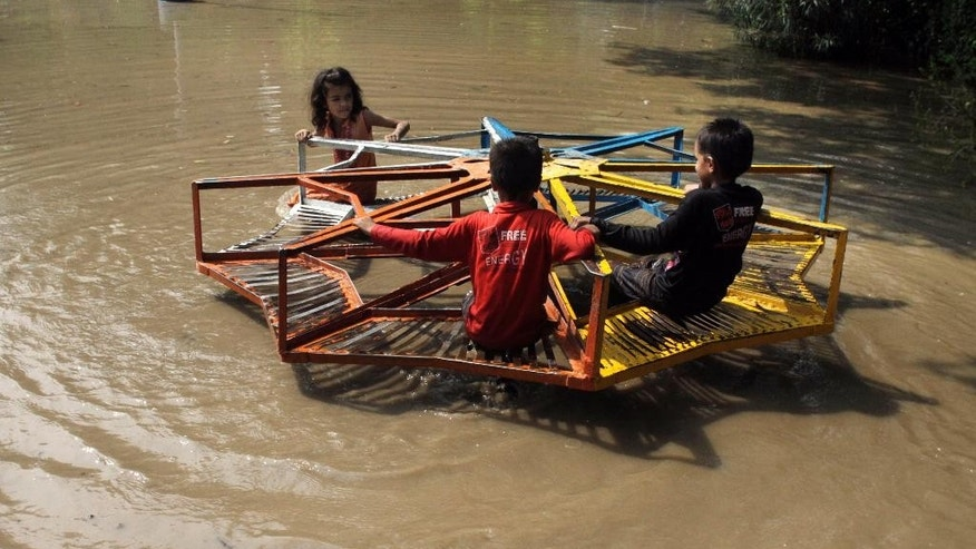 Pakistani children take a ride on a roundabout at a flooded park caused by heavy rains in Lahore, Pakistan, Tuesday, July 21, 2015. A Pakistani local government spokesman said this week's flash floods triggered by monsoon rains in the country's north have killed at least two people and damaged several homes, roads and bridges. (AP Photo/K.M. Chaudary)