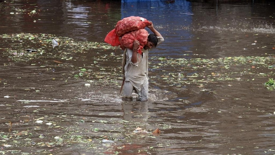 A Pakistani laborer carries sacks of potatoes while he wades through a flooded road caused by heavy rains in Lahore, Pakistan, Tuesday, July 21, 2015. A Pakistani local government spokesman says this week's flash floods triggered by monsoon rains in the country's north have killed at least two people and damaged several homes, roads and bridges. (AP Photo/K.M. Chaudary)