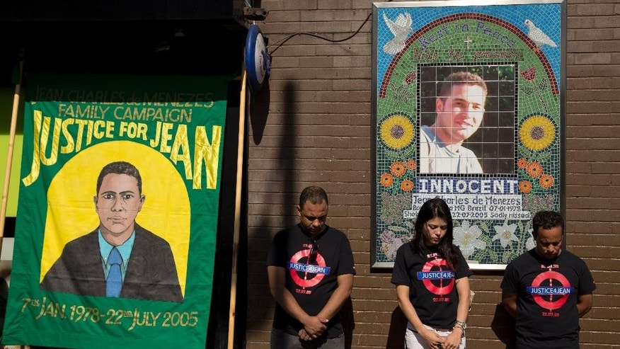 Cousins Alessandro Pereira, right, Vivian Figueiredo and friend Erionaldo da Silva, left, observe a minute's silence on the 10-year-anniversary of the death of 27-year-old Brazilian electrician Jean Charles de Menezes, shot by British police who thought he was a terrorist in the tense aftermath of deadly 2005 London subway bombings, at Stockwell station in London, Wednesday, July 22, 2015. Police shot de Menezes repeatedly on July 22, 2015 as he tried to board a subway train at Stockwell on his way to work, after they mistook him for a terrorist as he lived at the same building address as two bombing suspects. (AP Photo/Matt Dunham)