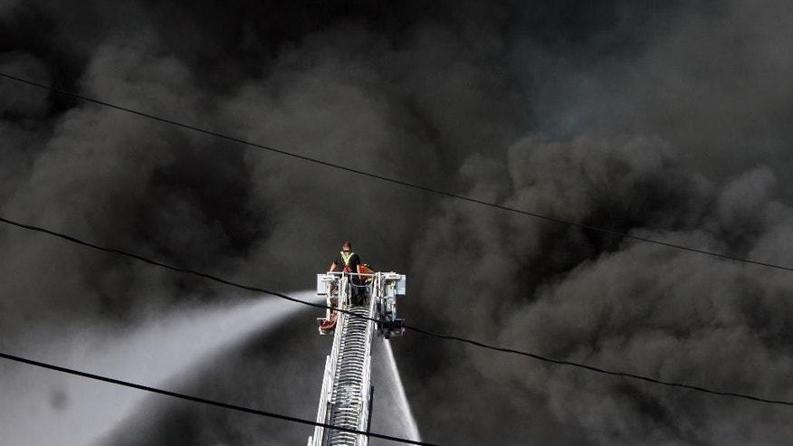 A firefighter battles a multiple alarm fire at a large warehouse in North Brunswick, N.J., Wednesday July 22, 2015. The warehouse fire in central New Jersey that was fueled by plastics, autos and household goods sent plumes of black smoke into the air Wednesday that were visible from space. (Mark R. Sullivan/Home News Tribune via AP)
