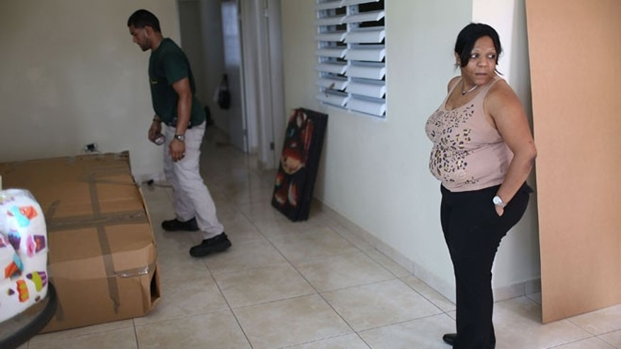 SAN JUAN, PUERTO RICO - JULY 01:  Yessenia Puente watches as movers from La Rosa del Monte moving company pack up her apartment as she prepares to move to Orlando, Florida this weekend on July 1, 2015 in San Juan, Puerto Rico. Puente joins a mass exodus of people fleeing the island due to increasing economic hardships and a financial crisis that has resulted in an estimated $72 billion public debt for the Puerto Rican government, which the governor has said is unpayable. The workers for the moving company, La Rosa del Monte, said that she is number 1465 that the company has packed for Orlando since the beginning of the year. (Photo by Joe Raedle/Getty Images)