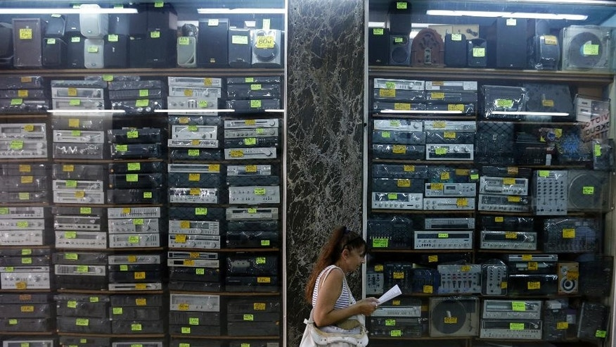 A woman reads a paper in front of a shop selling old stereo systems in Athens, Tuesday, July 21, 2015. Banks reopened Monday for the first time in three weeks. But for most Greeks, already buffeted by six years of recession, Monday was all about rising prices as tax hikes demanded by creditors took effect. (AP Photo/Thanassis Stavrakis)