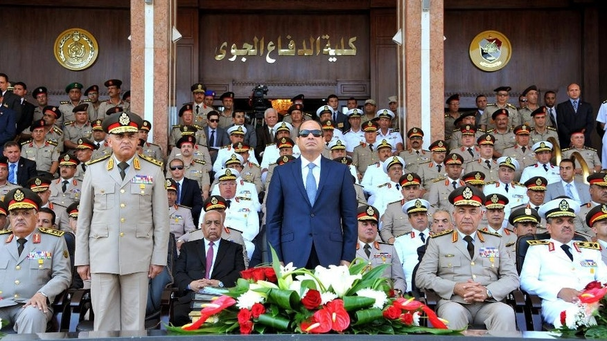 In this picture provided by the office of the Egyptian Presidency, Egyptian President Abdel-Fattah el-Sissi, center, and Defense Minister Sedqi Sobh, left, stand to attention while other members of the military look on at the Air Defense Academy in Alexandria, Egypt. The Egyptian president spoke to new military cadets on the occasion of the 63th anniversary of the officers' coup in 1952 that toppled the monarchy. (Mohammed Samaha/Egyptian Presidency via AP)