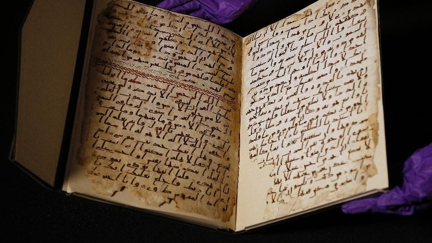 July 22, 2015: A university assistant shows fragments of an old Koran at the University in Birmingham, England. (AP Photo/Frank Augstein)