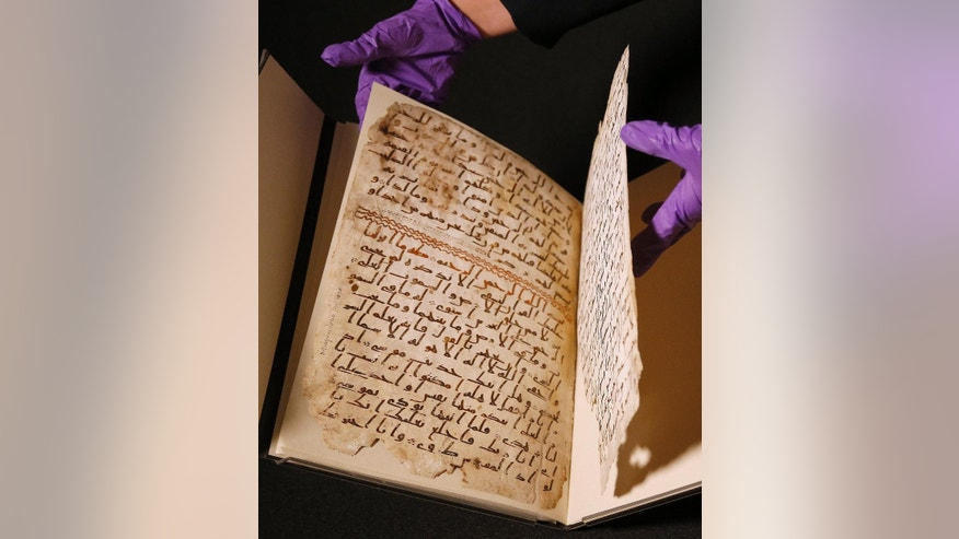 A university assistant shows fragments of an old Quran at the University in Birmingham, in Birmingham central England Wednesday, July 22, 2015. The University of Birmingham said Wednesday that scientific tests prove a Quran manuscript in its collection is one of the oldest known and may have been written close to the time of the Prophet Muhammad. Radiocarbon testing at Oxford University dated the parchment to the time of the prophet, who is generally believed to have lived between 570 and 632.(AP Photo/Frank Augstein)