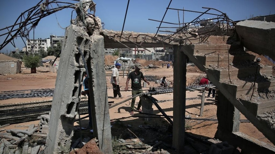 A Palestinian worker prepares rebar to rebuild a house which was destroyed during the last summer's war between Israel and Hamas, as the long-awaited reconstruction began in Shijaiyah neighborhood eastern Gaza City on Thursday, July 23, 2015. Construction has started on the first homes that will be rebuilt in the Gaza Strip since the devastating war destroyed much of the territory's infrastructure. (AP Photo/Khalil Hamra)