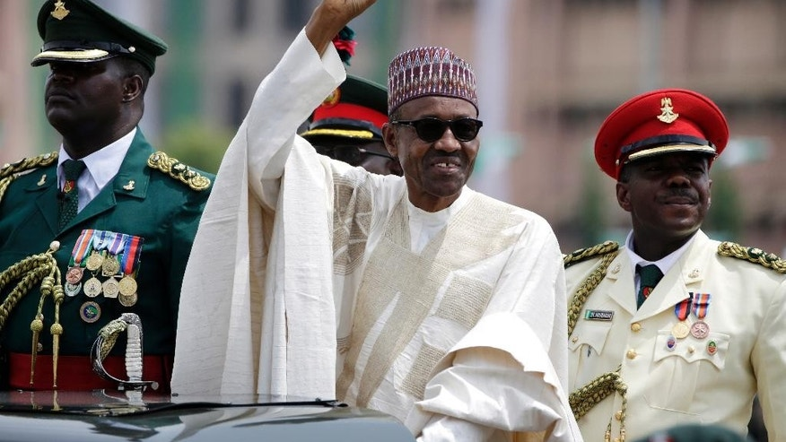 "FILE - In this Friday, May 29, 2015 file photo, Nigerian President Muhammadu Buhari salutes his supporters during his Inauguration in Abuja, Nigeria. Bomb blasts at two bustling bus stations killed 29 people and wounded 105, officials said Thursday, July 23, 2015 after Nigeria's new president warned that U.S. refusal to sell his country strategic weapons is ""aiding and abetting"" Boko Haram. (AP Photo/Sunday Alamba, File)"
