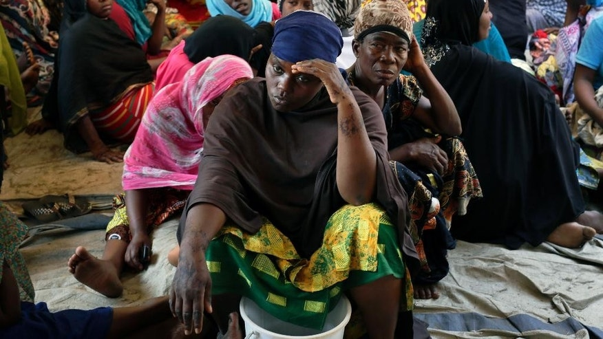 Women gather to mourn the death of a man killed during a robbery attempt by unidentified perpetrators in Bujumbura, Burundi, Thursday July 22, 2015.  Political motivated killings are not unknown in Burundi, but this man was killed when men tried to rob the shop he worked in.   Results for Tuesday's election will be announced Friday with Pierre Nkurunziza likely to win a third term after some opposition groups boycotted the polls.(AP Photo/Jerome Delay)