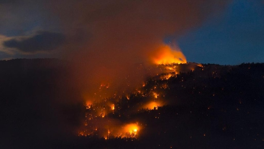 In this photo taken late Wednesday, July 22, 2015, a wildfire lights up a mountainside in West Kelowna, British Columbia. (Jonathan Hayward/The Canadian Press via AP) MANDATORY CREDIT