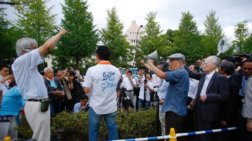 Japan's former Prime Minister Tomiichi Murayama, right, and protesters rally outside the Diet building during a rally in Tokyo, Thursday, July 23, 2015. Protesters gathered outside parliament, opposing a set of controversial bills intended to expand Japan's defense role at home and internationally. (AP Photo/Shizuo Kambayashi)