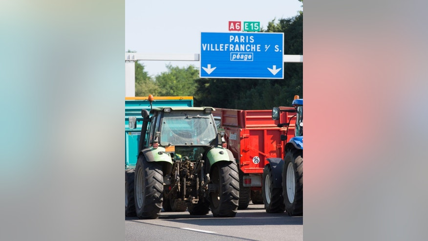 Farmers block the highway leading Paris to Lyon in Limonest near Lyon, central France, Thursday, July 23, 2015. Angry French farmers block the famed Mont Saint Michel causeway and highways leading to the Alps, hoping to get more government help for margins they say are being chipped way by cheap imports and pressure from grocery chains. Thursday's protests were a rejection of the government offer to back loans to the farmers and delay tax payments as part of a 600 million euro plan. (AP Photo/Vincent Dargent)