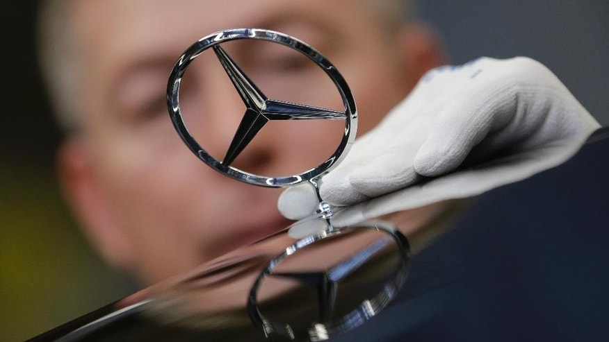 In this Jan 28, 2015 picture an employee attaches a Mercedes emblem as he assembles a Mercedes-Benz S-class model at the plant in Sindelfingen, Germany.  Daimler will present its second quarter earning Thursday, July 23, 2015.   (AP Photo/Matthias Schrader)