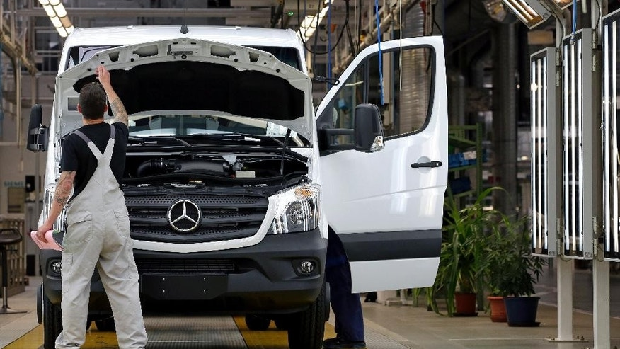 In this June 23, 2015 photo a man works on a van at the Mercedes-Benz automobile plant in Ludwigsfelde, near Berlin, Germany. Daimler will present its second quarter earning Thursday, July 23, 2015. (Photo/Michael Sohn)