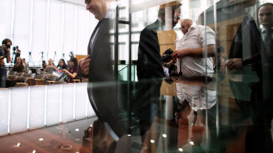 German Vice Chancellor and Economy Minister Sigmar Gabriel, left, passes a glass door as he arrives for a news conference in Berlin, Germany, Thursday, July 23, 2015. (AP Photo/Markus Schreiber)