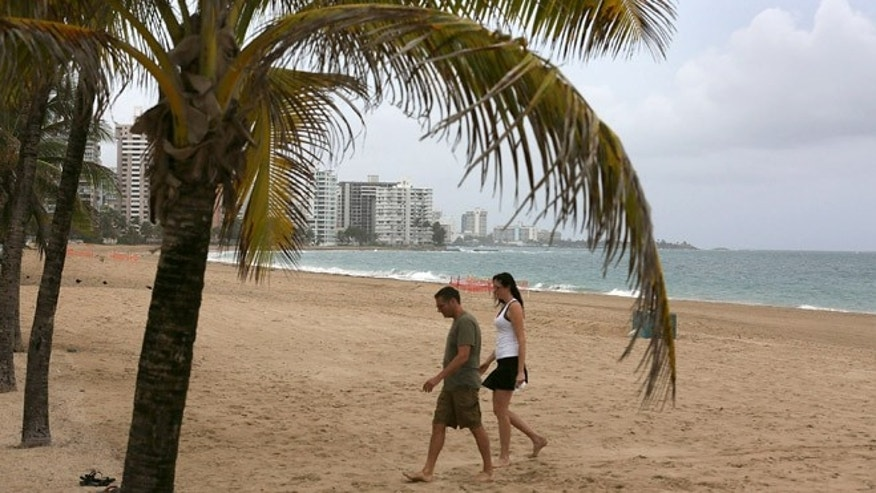 SAN JUAN, PUERTO RICO - JULY 01:  A couple walks on the beach on July 1, 2015 in San Juan, Puerto Rico. The island's residents are dealing with increasing economic hardships and a financial crisis that has resulted in the government's $72 billion debt.  Governor Alejandro Garcia Padilla said in a speech recently  that the people will have to sacrifice and share in the responsibilities for pulling the island out of debt. Consumer tax on certain items has risen to 11.5 percent. (Photo by Joe Raedle/Getty Images)