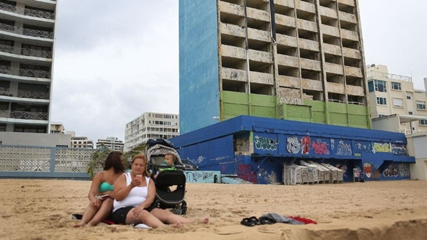 SAN JUAN, PUERTO RICO - JULY 01:  A family relaxes on the beach near the shell of a building on July 1, 2015 in San Juan, Puerto Rico. The island's residents are dealing with increasing economic hardships and a financial crisis that has resulted in the government's $72 billion debt.  Governor Alejandro  Garcia Padilla said in a speech recently  that the people will have to sacrifice and share in the responsibilities for pulling the island out of debt.  (Photo by Joe Raedle/Getty Images)
