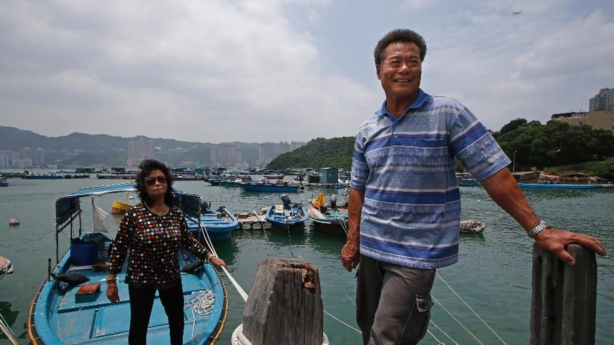 In this July 7, 2015 photo, Lai Tak-chuen, right, 68, a fish farmer, accompanied with his wife, speaks near his fish farm in Ma Wan of Hong Kong. Since China took control of Hong Kong from Britain in 1997, the city's billionaires have played a leading role in hewing the Asian financial center to Beijing's priorities. So too have a dwindling band of fishermen and farmers. (AP Photo/Kin Cheung)