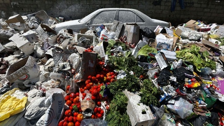 A car is seen between a pile of garbage covered with white pesticide in the Palestinian refugee camp of Sabra in Beirut, Lebanon.