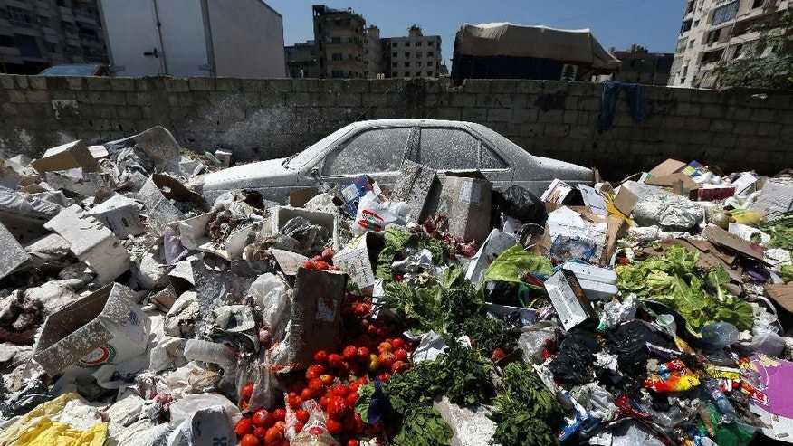 A car is seen between a pile of garbage covered with white pesticide in the Palestinian refugee camp of Sabra in Beirut, Lebanon, Thursday, July 23, 2015. The Lebanese cabinet has failed to agree on a solution for the country's growing garbage crisis, postponing discussion until next week as trash piles up on the streets. (AP Photo/Bilal Hussein)