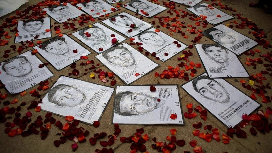 FILE - In this March 26, 2015 file photo, drawings of some of the 43 missing students from a teachers college are surrounded by flower petals, forming the shape of a heart, during a protest marking the six-month anniversary of their disappearance, in Mexico City. In a report issued Thursday, July 23, 2015, Mexico's National Human Rights Commission is questioning the government's official version of what happened to the missing students in Guerrero state who investigators say were killed and incinerated last September. (AP Photo/Rebecca Blackwell, File)