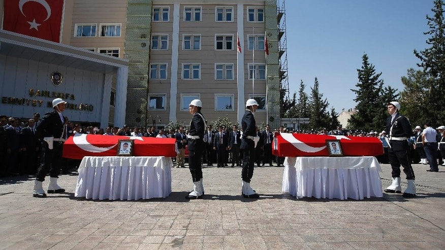 Turkish police officers stand in attention on front of the coffins of police officers Feyyaz Yumusak and Okan Acar, during a funeral procession in Sanliurfa, southeastern Turkey, Thursday, July 23, 2015. The officers were found shot dead in their home in the town of Ceylanpinar, located near Turkey's border with Syria, in an attack that was not immediately clear if it was terrorism-linked. The assault came after a bomb attack on Monday in the nearby the town of Suruc, also near the Syrian border, killed 32 people and wounded nearly 100. (AP Photo/Emrah Gurel)