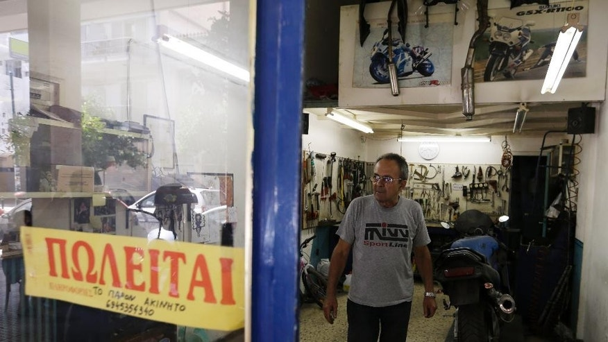 Mechanic Giorgos Prasinoudis steps out of his closed motorcycle repair shop, as a 'For Sale' sign is posted on the front window, in Athens, on Wednesday, July 22, 2015. Uncertainty over Greece's bailout and recent capital controls have led to a new spate of store closures in Greek capital. (AP Photo/Thanassis Stavrakis)