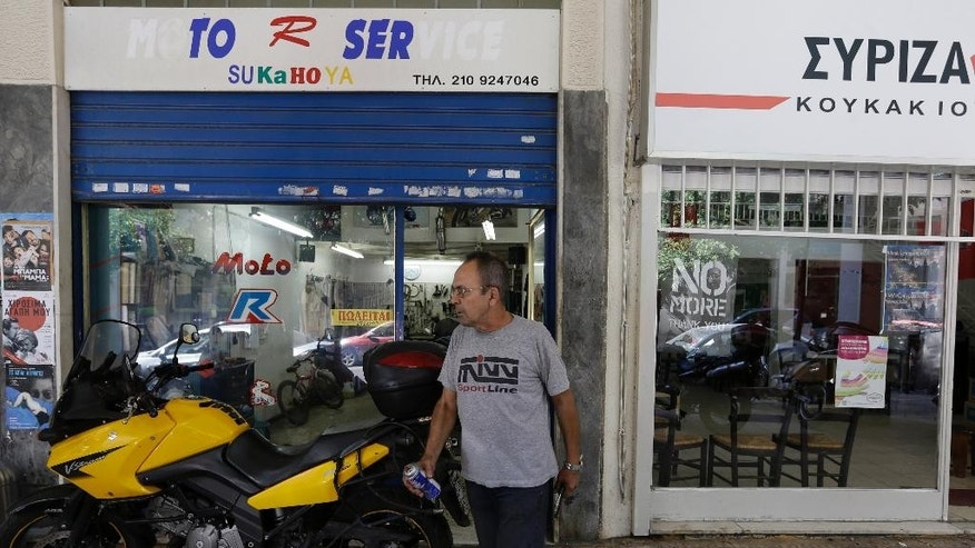 Mechanic Giorgos Prasinoudis steps out of his closed motorcycle repair shop, as a 'For Sale' sign is posted on the front window, next to Syriza's governing party local office in Athens, on Wednesday, July 22, 2015. Uncertainty over Greece's bailout and recent capital controls have led to a new spate of store closures in Greek capital. (AP Photo/Thanassis Stavrakis)