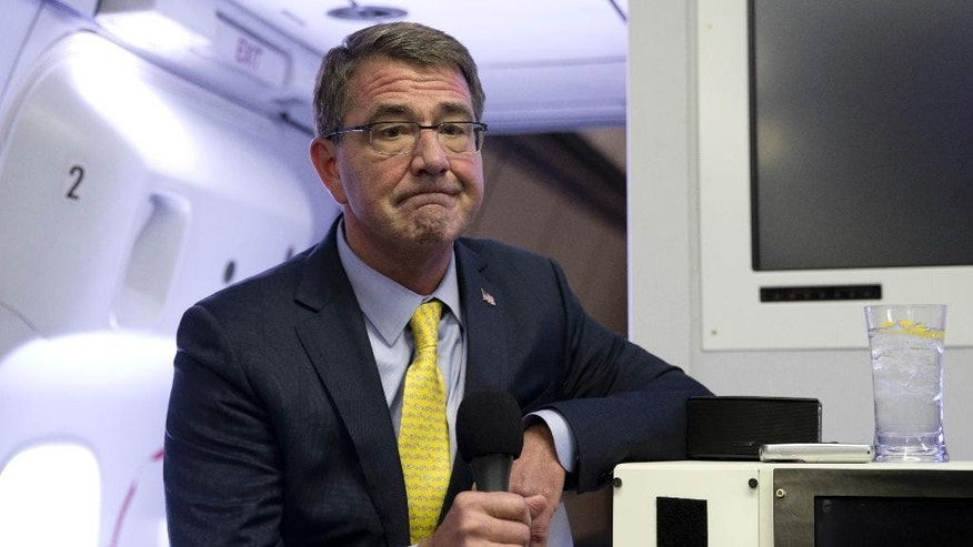 FILE - In this Wednesday, July 22, 2015, file photo, U.S. Defense Secretary Ash Carter pauses as he speaks with media on a military aircraft after departing Jiddah, Saudi Arabia, en route Amman, Jordan. Carter arrived unannounced in Baghdad on Thursday, July 23, 2015, to assess the government's progress in healing the country's sectarian divisions and hear the latest on support for the Iraqi army's coming attempt to recapture the key city of Ramadi from the Islamic State. (AP Photo/Carolyn Kaster, Pool, File)