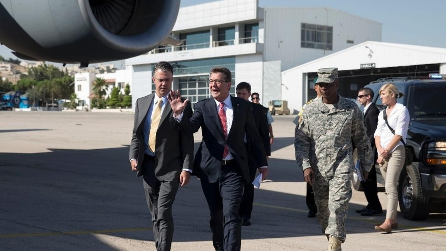 U.S. Defense Secretary Ash Carter, joined by U.S. Army Lt. Gen. Ron Lewis, right, and Chief of Staff Eric Rosenbach, left, boards his plane at Queen Alia Airport in Amman, Jordan, Thursday, July 23, 2015, en route to Baghdad, Iraq. Carter is on a week long tour of the Middle East focused on reassuring allies about Iran and assessing progress in the coalition air campaign against the Islamic State militants in Syria and Iraq. (AP Photo/Carolyn Kaster, Pool)