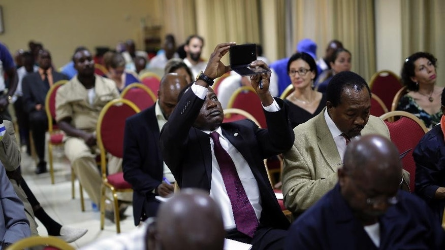 A guest photographs a powerpoint presentation showing the preliminary results of Burundi's Presidential elections as they are being presented by the National Electoral committee in Bujumbura, Burundi, Friday July 24, 2015. Burundi's electoral chief says President Pierre Nkurunziza has won a third term in office, amid unrest over whether his third term is constitutional.  (AP Photo/Jerome Delay)