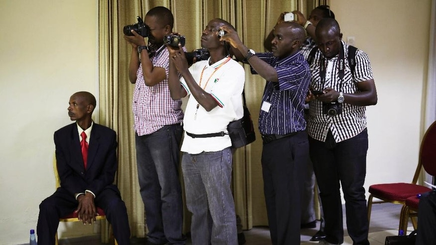 Photographers take pictures of a powerpoint presentation showing the preliminary results of Burundi's Presidential elections as they are being presented by the National Electoral committee in Bujumbura, Burundi, Friday July 24, 2015.  Pierre Nkurunziza wins a third term with 69.41 percent of the votes. (AP Photo/Jerome Delay)