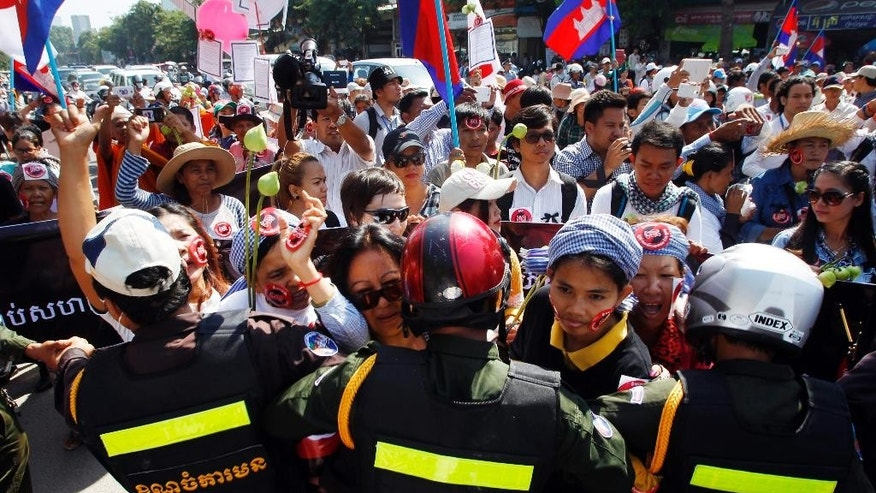 Protesters are blocked by riot police officers as they march toward the Senate building during a vote on the civil society law in Phnom Penh, Cambodia, Friday, July 24, 2015. Senators of the ruling Cambodian People's Party approved the controversial draft law Friday that has been boycotted by the oppositional party. The Law on Associations and Non-Governmental Organizations tightly regulates all non-governmental organizations in the country and grants the government sweeping powers to clamp down on civil society activities it deems to be a threat to national security. (AP Photo/Heng Sinith)