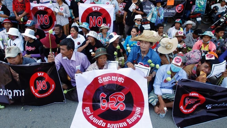 "Protesters sit on a main street with stickers that read: ""Say No! Union, Association and NGO Laws""  during they stage a rally in front of the Senate building where senators hold their session to vote the draft of the Association and NGO Laws, in Phnom Penh, Cambodia, Friday, July 24, 2015. Senators of the ruling Cambodian People's Party approved a controversial draft law Friday that has been boycotted by the opposition party. The Law on Associations and Non-Governmental Organizations tightly regulates all non-governmental organizations in the country and grants the government sweeping powers to clamp down on civil society activities it deems to be a threat to national security. (AP Photo/Heng Sinith)"