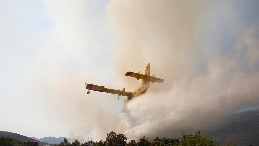 Croatian firefighters work to control a large forest fire in the village of Zabrdje on the Peljesec peninsula in southern Croatia, Friday, July, 24, 2015. Volunteers, military and Croatian firefighters are struggling to cope with raging forest fires on the country's Adriatic coast. The Peljesac peninsula is facing a blaze that has forced hundreds of residents and tourists to evacuate. (AP Photo/Amel Emric)