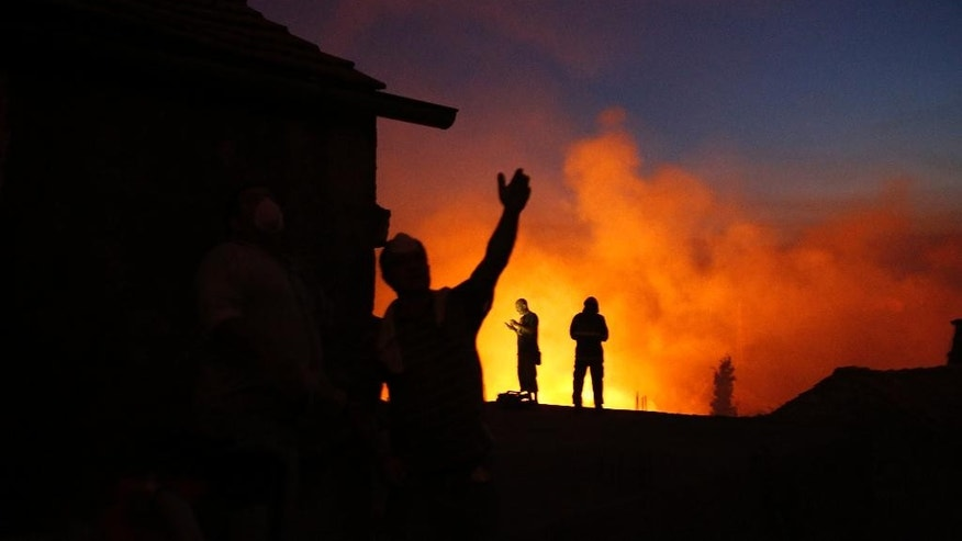 Croatian fire workers try to control a large forest fire in the village of Ponikve on the Peljesec peninsula in southern part of Croatia, Thursday July 23, 2015. Volunteers, military and Croatian fire fighters are struggling to cope with raging forest fires on its Adriatic coast. The biggest blaze has forced hundreds of residents and tourists to evacuate, at the height of the tourist season. (AP Photo/Amel Emric)