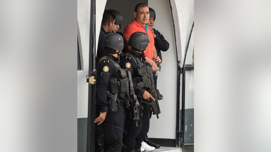 Guatemalan drug trafficking suspect, Jairo Orellana Morales, is escorted by police to an aircraft prior to his extradition to the U.S. at an Air Force base in Guatemala City, Friday, July 24, 2015. Orellana, an alleged member of the Zetas drug organization in Guatemala, faces federal drug trafficking charges in Washington. (AP Photo/Luis Soto)