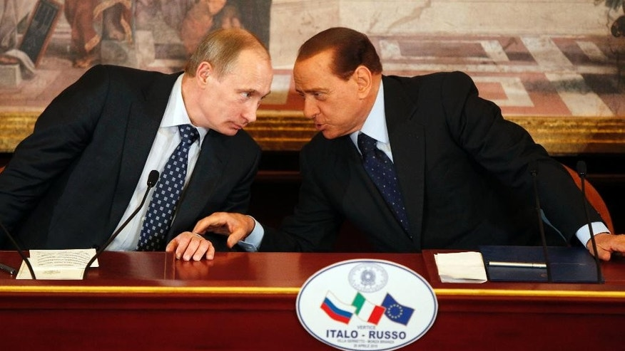 "FILE -- In this April 26, 2010 file photo, then Italian Premier Silvio Berlusconi, right, and Russian President Vladimir Putin talk during a press conference at Villa Gernetto, in Gerno, near Milan, Italy. The Kremlin is denying that President Vladimir Putin offered to make Silvio Berlusconi his economy minister, though he did extend ""metaphorical support"" to Italy's embattled ex-premier. (AP Photo/Luca Bruno, File)"