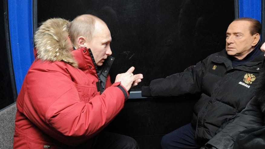 "FILE -- In this March 7, 2012 file photo, Vladimir Putin, left, gestures talking to former Italian Prime Minister Silvio Berlusconi as they sit in a gondola lift during their meeting in the mountain resort of Krasnaya Polyana near the Black Sea resort of Sochi, southern Russia. The Kremlin is denying that President Vladimir Putin offered to make Silvio Berlusconi his economy minister, though he did extend ""metaphorical support"" to Italy's embattled ex-premier.  (Alexei Druzhinin/RIA-Novosti, Goverment Press Service via AP, File)"