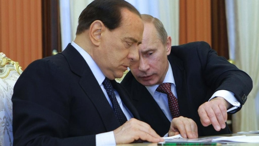 "FILE -- In this Oct. 22, 2009 file photo, Russian President Vladimir Putin, right, and former Italian Prime Minister Silvio Berlusconi share a word during a meeting with Russian businessmen in St. Petersburg, Russia. The Kremlin is denying that President Vladimir Putin offered to make Silvio Berlusconi his economy minister, though he did extend ""metaphorical support"" to Italy's embattled ex-premier. (Alexei Nikolsky/RIA-Novosti, Goverment Press Service via AP, File)"