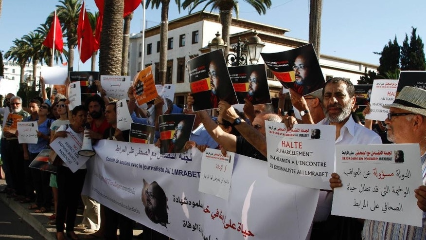 Journalists and activists wave banners and chant slogans in support of editor Ali Mrabet in front of parliament in Rabat, Morocco on July 24, 2015. Moroccan journalists and activists are calling on the government to end the harassment of hunger striking Mrabet. (AP Photo/Paul Schemm)